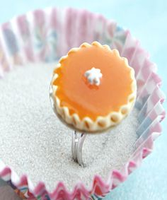 This ring features a miniature handmade pumpkin pie sculpted from polymer clay. The pie measures about an inch in diameter and is securely attached to an adjustable silver tone ring that fits most rin