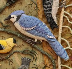 Mavor; After looking at photos of bluejays, I picked a pose and cutthe body shape out of matt board. Then I cut a piece of white felt and stitched a textured pattern on the breast.I cut a whole in the felt for the bead eye, too.