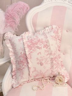 Pretty pink toile pillow........& a striped chair, charming......oh the pearls too.