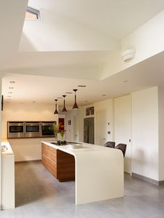Kitchen counter extends into table and curves to floor in one continuous flow