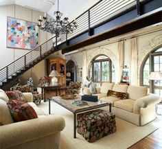 A modern steel staircase and large abstract painting mix with an antique French armoire and plush couches in this unique home.