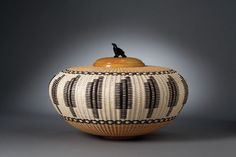 """FEATHERS""  Joan Brink  Natural, bleached and dyed cane, satinwood rim, base and lid;  jet Raven by Calvert Bowannie (Zuni)"