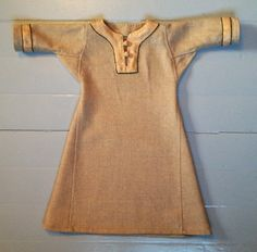 Viking tunic for a baby´s name giving. Length 54 cm, sleeves 18 cm. Fine wool, herringbone silk and natural dyed wool yarn on thin decorative embroideries around the silks.