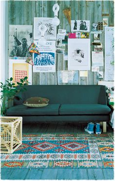 Cool rustic boho living space. Teal sofa, kilim rug, vintage art.