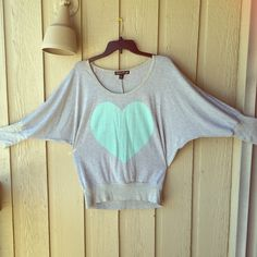 Forever 21 Batwing-sleeved Heart Sweatershirt Brand: F 21 (living doll). I bought this in Forever 21, so just typed it as that.        Size: XL        Color: grey, with a light green heart.         ⚠️The trademark doesn't been sewed very well, so it can be seen from the back, plz see the last pic. Forever 21 Tops Sweatshirts & Hoodies