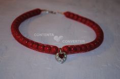 Perle di colore rosso in un tubolare di rete rossa, con pendente a forma di cuore.