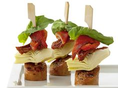 Italian sausage, artichoke hearts, roasted red peppers and fresh basil on skewers for a hearty, healthy appetizer.