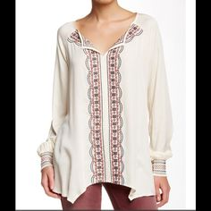 Democracy Split Neck Embroidered Tunic Raglan sleeves frame the neckline of this Sharkbite hem top, features embroidered detailing at the center front and smocked cuffs..100% Rayon Democracy Tops Tunics