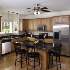 Oak Cabinets with stainless and white appliances and black countertop