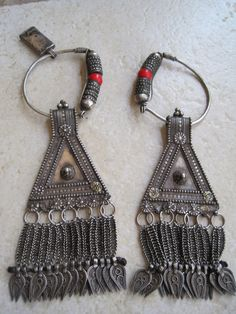 Oman | Pair of antique Bedouin head ornaments.  High grade silver, 90 - 92%. | This head ornament was given to a bride to wear on her wedding day. It was hung on a leather band over the head, framing the face, so that the pendants (the triangular part with the dangles) would look like earrings. | t is noteworthy that Bedouin jewelry in general and Omani in particular was not passed down. A new bride did not want someone else's jewelry. It was melted down and reshaped into new jewelry.