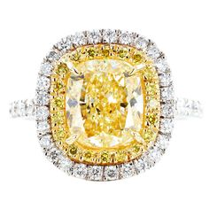 3.04ct Fancy Yellow Diamond Ring $42,500.  Two tone 18 karat yellow and white gold solitaire ring consisting of 1 cushion cut natural canary diamond weighing 3.04 carats measuring 8.50 x 7.50 x 5.00mm, the stone is set with .82 carats total weight of full cut colorless and canary diamonds.