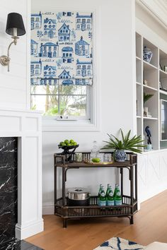 Hamptons-inspired living room with blue accents, rattan bar cart next to fireplace. Hamptons Style Homes, The Hamptons, Waterfront Homes, Step Inside, Stone Gallery, Gold Coast, Custom Cushions, Arched Windows