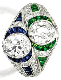 Platinum, Diamond, Demantoid Garnet and Sapphire Ring, Charlton & Co. Set with two old European-cut diamonds together weighing approximately 1.70 carats, accented by calibré-cut demantoid garnets and sapphires, the mounting further set with smaller old European-cut diamonds weighing approximately 1.25 carats, size 5, signed Charlton; circa 1920.