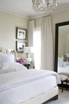 chic, elegant soft cream bedroom design with sand beige paint color walls, cream silk drapes, espresso wood brown floor mirror, white bench, cream tufted wingback headboard bed, crisp white bedding, white lamp, black nightstands, champagne gilt picture frames, silver chandelier, and crown molding. Sand beige tan white espresso brown pink bedroom colors.