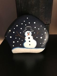 My First attempt at a painted rock ...My mind goes to a snowman ...first one I painted was a snowman face ...