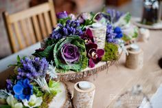 Wooden pedestal table centrepieces with fresh blooms and candles. Flowers by Blooming Bridal