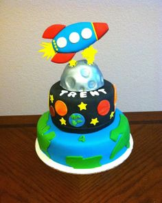 Outer space theme. Rocket ship, earth, planets, moon, solar system, fondant vegan cake.