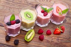 Drink smoothies four summer strawberry, blackberry, kiwi, raspberry on wooden table.