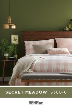 For a timeless color combination, start with BEHR? Paint in Secret Meadow. This deep green wall color pairs beautifully with the pink gingham bedspread and wood headboard in the room, creating a comfortable and soothing style. Click below for full color details to learn more.
