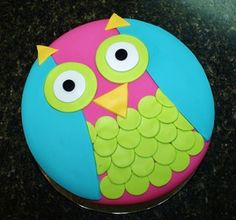Owl cake in bright colors for a baby shower.