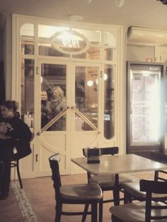 Café Los Alpes, La Carolina. Cette photo est prise à l'intérieur du café. Au premier plan on peut voir une table vide, avec des chaises. Au deuxième plan, devant la porte d'entrée, deux clients viennent d'arriver et se saluent. Au fond, on aperçoit des clients qui sont sur le point d'entrer dans le café. La table vide les attend. C'est un samedi soir de novembre.