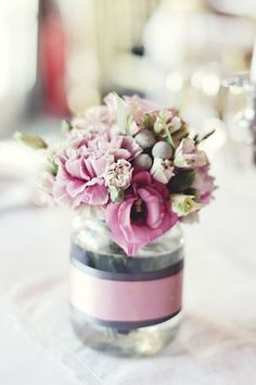 White Carnations and small blue flowers. Blue and ivory ribbons instead. For sure centerpieces.  The finished product ~ Small hand tied arrangements in jam jars decorated with ribbon.