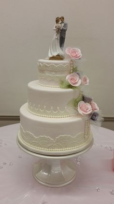 Lace and pearls shimmer to complete this vintage inspired wedding. #vintageweddingcake #vintagelacepearlsweddingcake #weddingcakegumpasteroses
