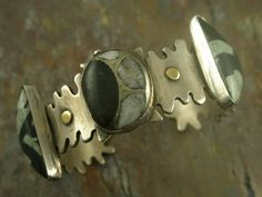 Cuff | Victoria Maase Stoll.  Sterling silver,18 k. gold and holds Chinese writing rock (jasper) and pyratized amonite.