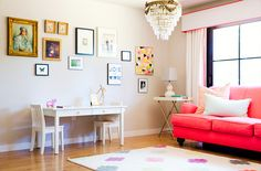Colorful and pattern-packed living room with bright sofa, gallery wall, children's play table and chandelier