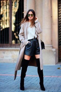 Street style look blusa branca, shorts de couro preto, sobretudo bege e bota over the knee.