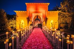 restaurant wedding venue marrakech morocco flowers candles opulent traditional wedding buildingAn aisle of flower petals lined with lanterns leading up to a beautiful ceremony site in Marrakech, Morocco.