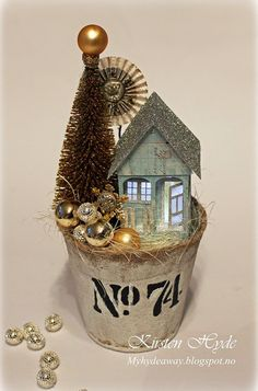 Christmas Glitter house scene in a Peat Pot. The house is made with papers from Prima. Template for the house in the blog. Made by Kirsten Hyde
