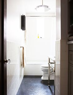 White and neutral bathroom with bright natural light and industrial light fixture