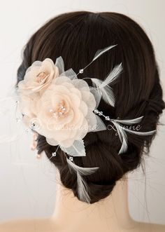Three blush organza flowers with rhinestone accented centers and wispy, Swarovski crystal adorned ivory feathers create this timely bridal hair flower clip. It is 5 inches long and 3.25 inches high, o
