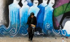 """Street artist Shamsia Hassan is featured in front of one her graffiti creations in an industrial park in Kabul, Afghanistan. She says: """"If we can do graffiti all over the city, there will be nobody who doesn't know about art."""" Hassan's comments about street art go to the heart of much of Bourdieu's work on taste and distinction. http://othersociologist.com/2012/02/25/street-art-and-distinction-in-kabul-afghanistan/"""