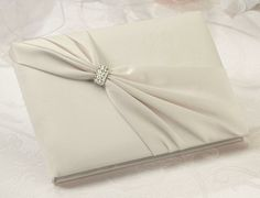 Ivory Sash Wedding Guest Book covered in ivory satin and features an ivory satin band that stretches diagonally over the cover. The band is gathered in the middle and decorated with a rhinestone band.