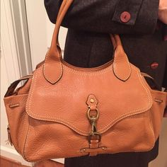 Cole Haan Leather Purse Stunning & classy pebbled leather in a tan color great year round! Many pockets and lovely toggle detail in the front & tassels on the sides! Can be worn on your arm or on your shoulder!! Some wear on the label & the inside of the handles but otherwise in fantastic condition! Cole Haan Bags