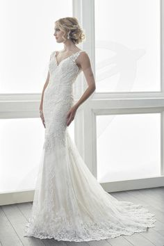 Jacquelin Bridals Canada - 15625 - Wedding Gown - Lace adorns the body of this stunning gown. Border lace, placed around the hem of the gown, compliments the lace used on the body. This dress features a stunning open back and has buttons that cover the back zipper. The dress is finished with a stretch lining for added comfort.