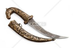 heavily decorated knife - A knife with gold detailing on the handle and a design stamped into the blade on a white background.