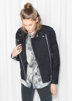 Crafted from smooth suede, this edgy biker jacket features padded shoulder, zipped waist pockets, and shiny hardware details with a luxe, silver-tone surface.