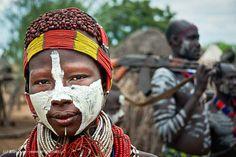Um jovenzinho da etnia Karo / Kara,  morador do Vale do Rio Omo, na Etiópia, exibe pintura corporal, penteado e acessórios característicos de seu povo. Qualquer cor é utilizada na pintura do corpo,  a argila branca é a mais comum, mas podem usar o pigmento vermelho do ferro, o negro do carvão ou o ocre da terra. Pintar o corpo é um jogo, faz parte do prazer de ser diferente. Fotografia: Jean Buet.