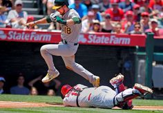 Clearing the catcher -    Oakland Athletics' Ben Zobrist, left, jumps over Los Angeles Angels catcher Chris Iannetta as he scores on a ball hit by Eric Sogard during the second inning on June 14 in Anaheim, Calif. Iannetta was charged with an error on the play. The Athletics won 8-1. -   © Mark J. Terrill/AP Photo