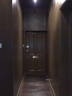 Brown door at the end of a brown hallway.