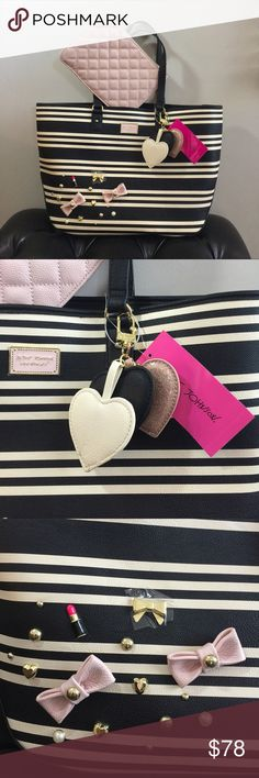 """Betsey Johnson Stripe Tote 2pc set This tote comes with a wristlet. Snap Tab closure and dual carrying handles with 9"""" drop. It has silky lined interior with 1 zip pocket and 2 slip pockets. Comes with ❤️ shaped charms in 3 different colors. Lipstick and pink bow decoration on the front of the Tote. Gonna Love it!! Betsey Johnson Bags Totes"""