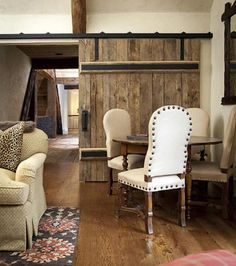 Natural wood plank and wrought iron sliding interior barn door - Francie Hargrove via Atticmag