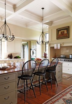 Windsor stools from New Hampshire furnituremaker Bill Morse pull up to a spacious island in this lofty kitchen, complete with grand views of peaks and valleys of Mount Washington - Traditional Home® Photo: Jonny Valiant and Joseph St. Pierre Design: Nancy Gould