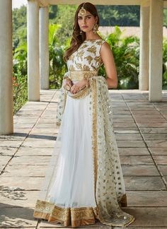 White and Gold Embroidered Net Anarkali features a net kameez with dhupioni silk bust and santoon inner, santoon bottom and embroidered net dupatta. Embroidery work is completed with zari, stone, sequins and lace embellishments. Indian Bridesmaid Dresses, Asian Wedding Dress, Indian Bridal Outfits, Indian Bridal Lehenga, Indian Gowns, Pakistani Dresses, Indian Wear, Anarkali Dress, Anarkali Suits