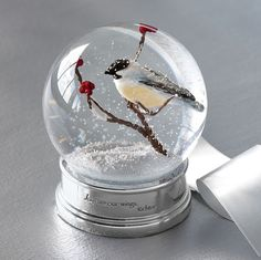 "ODE TO JOY SNOW GLOBE -- A black-capped chickadee perches within our snow globe's flurry…an expression of the quote engraved on the base, ""Joys are our wings."" Glass globe"