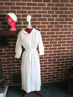 """Vintage 1920s Nurse Uniform Including White Linen by funoldstuff, $59.00---This fabulous nurse's uniform from a midwest estate dates to the 1920s or a bit earlier and iis in excellent condition with no problems. The linen dress has hook & eye closures up the front...it fits the mannequin perfectly so is 32"""" at the bust and 25"""" at the waist. The white cotton cap has a couple of tiny age-related spots of discoloration."""