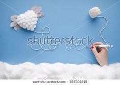 """Women hand writing the word """"Love"""" with white string attached to a white flying heart with feather wings, in a heavenly scenery with clouds made of cotton-wool, on  a blue sky paper background."""